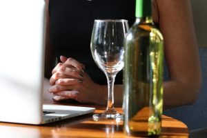 Woman's hands clasped in front of laptop with bottle of white wine and glass