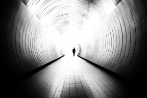 Man walking in between two huge tunnel walls, showing visually how you can diminish yourself or your abilities when presenting your ideas.