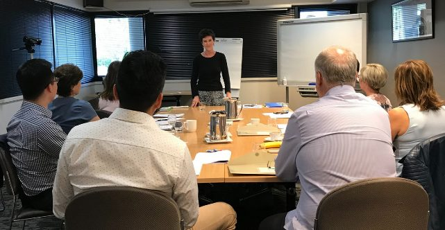 Sarah Denholm standing in front of a table training a small group class in the complete presentation skills course melbourne